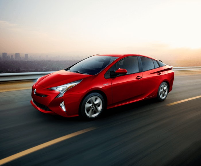 Exterior view of the Prius Four Touring in red being driven with an urban landscape in the background.