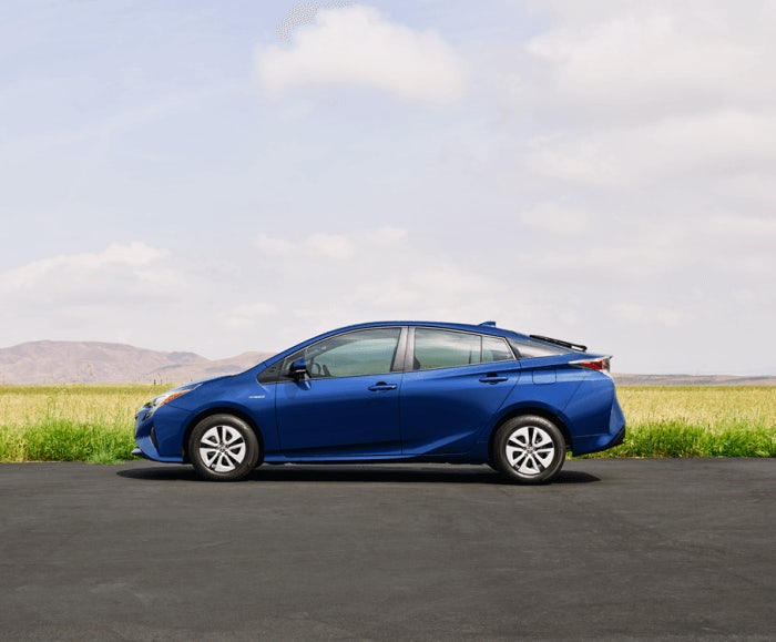 Lateral exterior view of the Toyota Prius Two in blue while parked next to a green field.