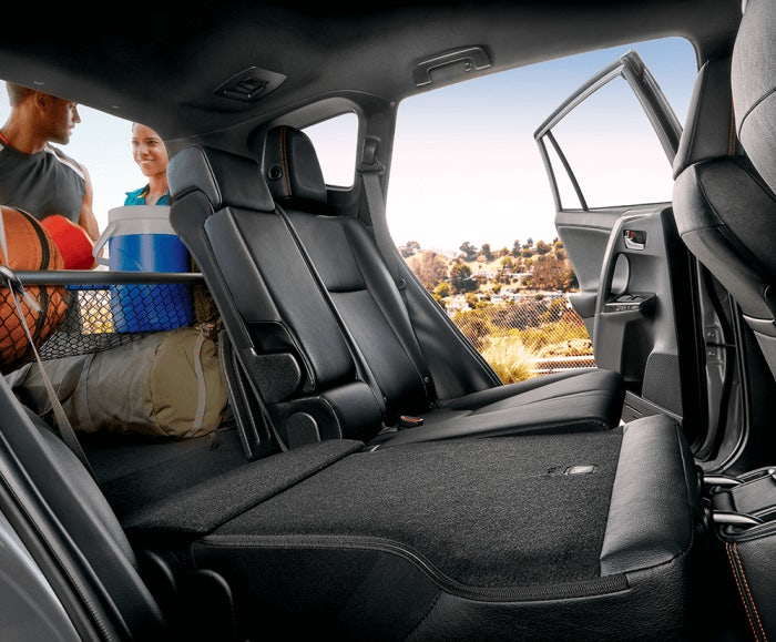 Interior shot of the RAV4 SE's rear seats and cargo space with 60/40 split folding seats and black interior trim.