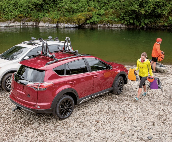 Rear angled view of the RAV4 XLE in Ruby Flare Pearl parked by a river with a woman holding lifejackets by the passenger-side door.