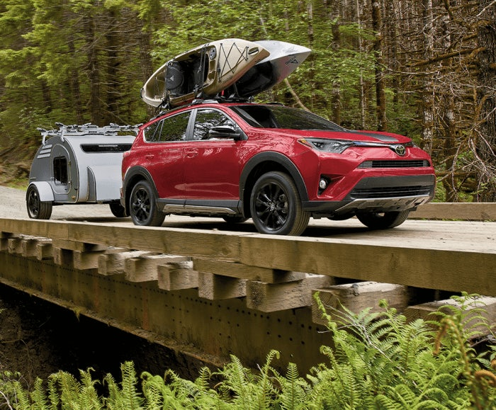 Dual shot of the RAV4 Adventure in Ruby Flare Pearl and the RAV XLE in Magnetic Gray Metallic driving on a forest trail over a bridge. The RAV4 Advenureis carrying a kayak on its roof rack and pulling a trailer.