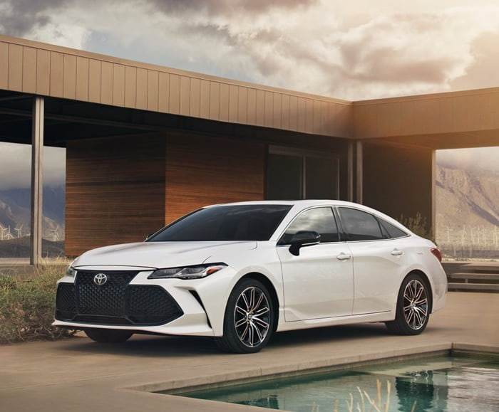 Driver side exterior view of 2019 Avalon Touring in Wind Chill Pearl parked in a driveway in front of a residence.