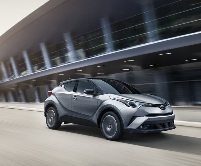 Side-angled shot of the 2019 C-HR limited in silver knockout metallic driving at speed in an urban area.