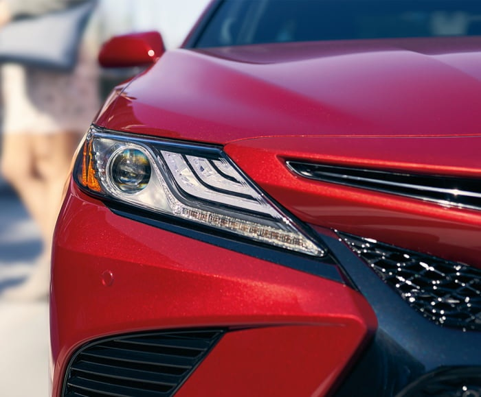 Front-facing shot of static headlight and front bumper of 2018 Camry in Supersonic Red.