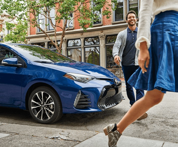 Side-facing shot of the 2017 Toyota Corolla SE in Blue Crush Metallic parked on a city street with people walking by.