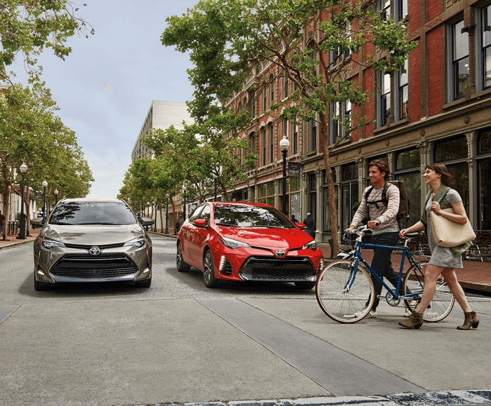 Front-facing view of the 2017 Toyota Corolla LE and XSE in Classic Silver Metallic and Barcelona Red Metallic stopped at a crosswalk in an urban area.