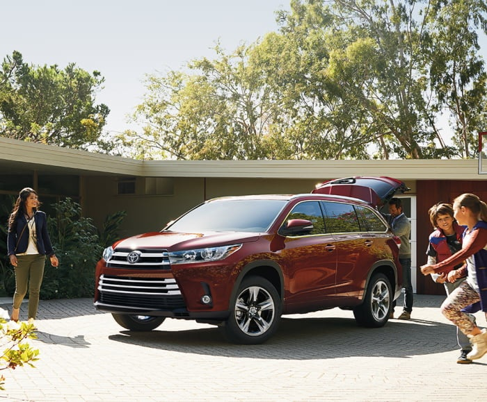 Front-angled shot of the 2019 Highlander limited in Ooh La La Rouge Mica parked in front of a family home.