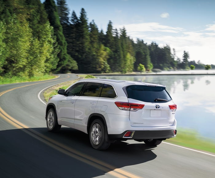 Rear action shot of the 2019 Highlander Hybrid Limited in Blizzard Pearl driving along a forest road.