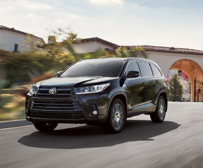 Front-angled shot of the 2017 Highlander SE in Midnight Black driving in a residential area.