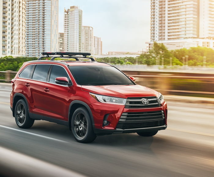 Action-Perfomance shot of the 2019 Highlander SE in Salsa Red Pearl on a bridge with body of water and city in background.