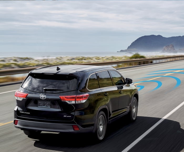 Rear-angled shot of the 2018 Highlander SE in Midnight Black Metallic using sonar with the 2018 Highlander Hybrid in Blizzard Pearl driving in front.