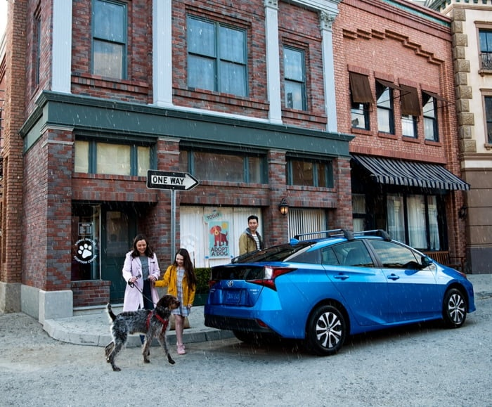 Family and large dog exit cafe to enter 2019 Prius in Storm Blue on city street.