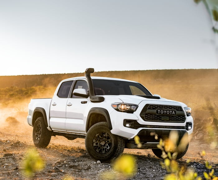 Side-angled shot of the Toyota Tacoma TRD Pro in Super White driving on a desert off-road.