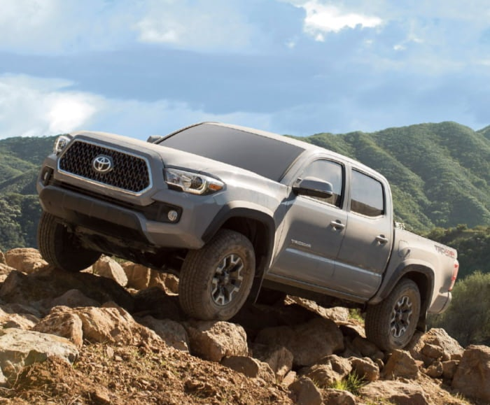 Side-angled view of the Toyota Tacoma TRD Off-Road Double Cab shown in Cement traversing over boulders.