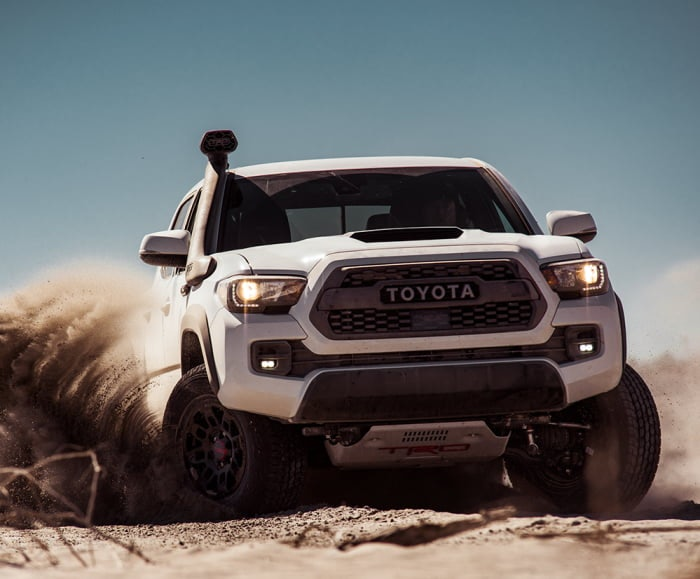 Front-facing shot of the Toyota Tacoma TRD Pro in Super White driving through a desert landscape.