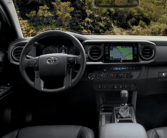 Interior front-facing shot of the Toyota Tacoma TRD Pro in black with steering wheel and infotainment system in view.