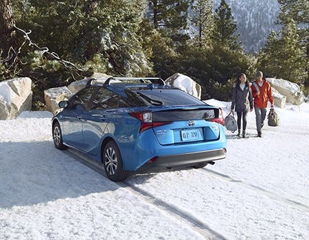 Prius XLE AWD-e shown in Electric Storm Blue with available accessory cargo cross bars.